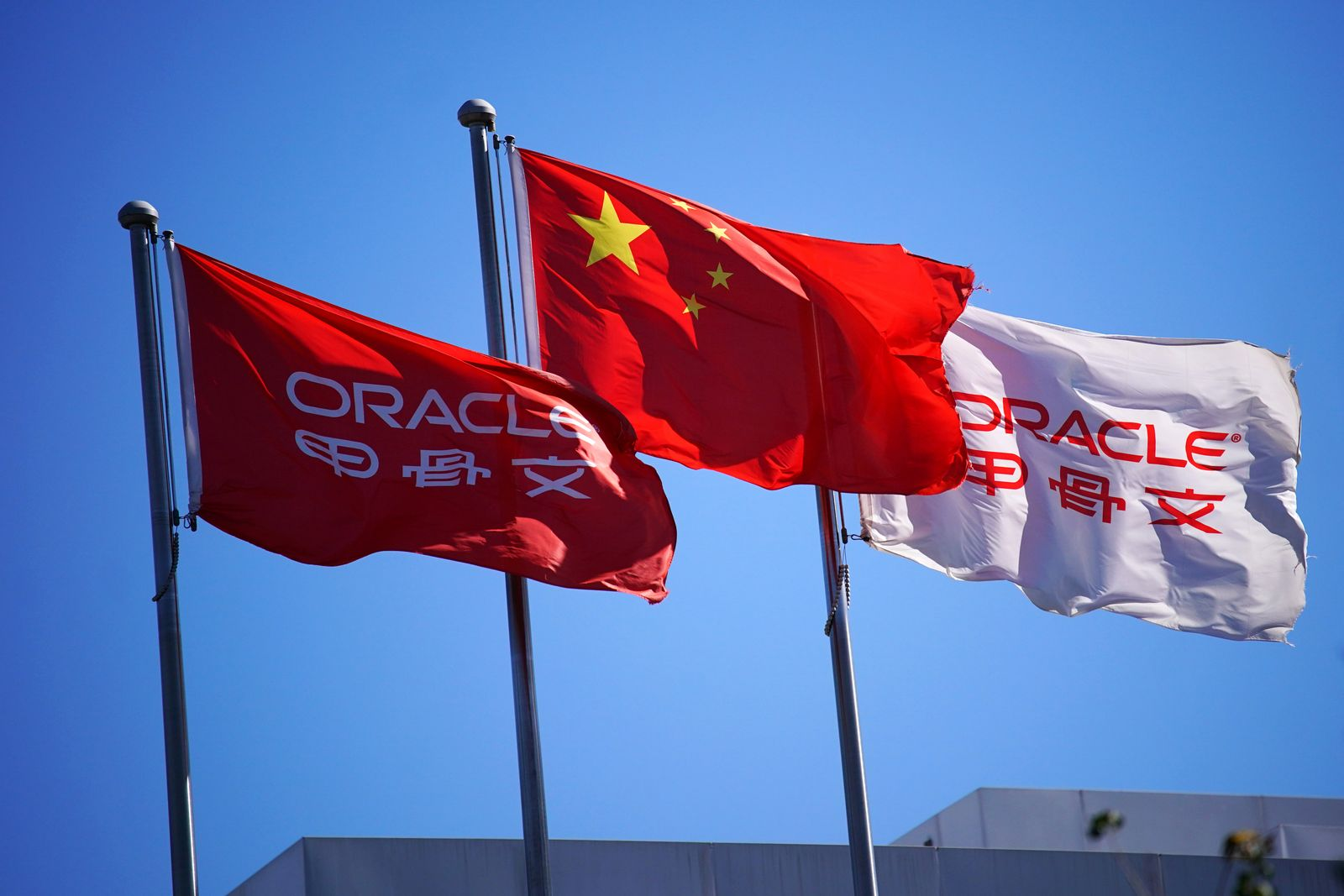 Chinese National flag flutters among flags of Oracle at its office buildings in Beijing