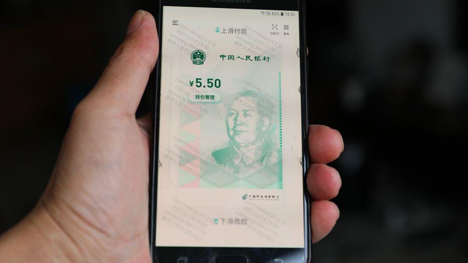 Künftig keine Münzen und Scheine mehr? Ein digitaler Yuan erscheint auf einem Smartphone mit der Silhouette von Mao Tse-tung