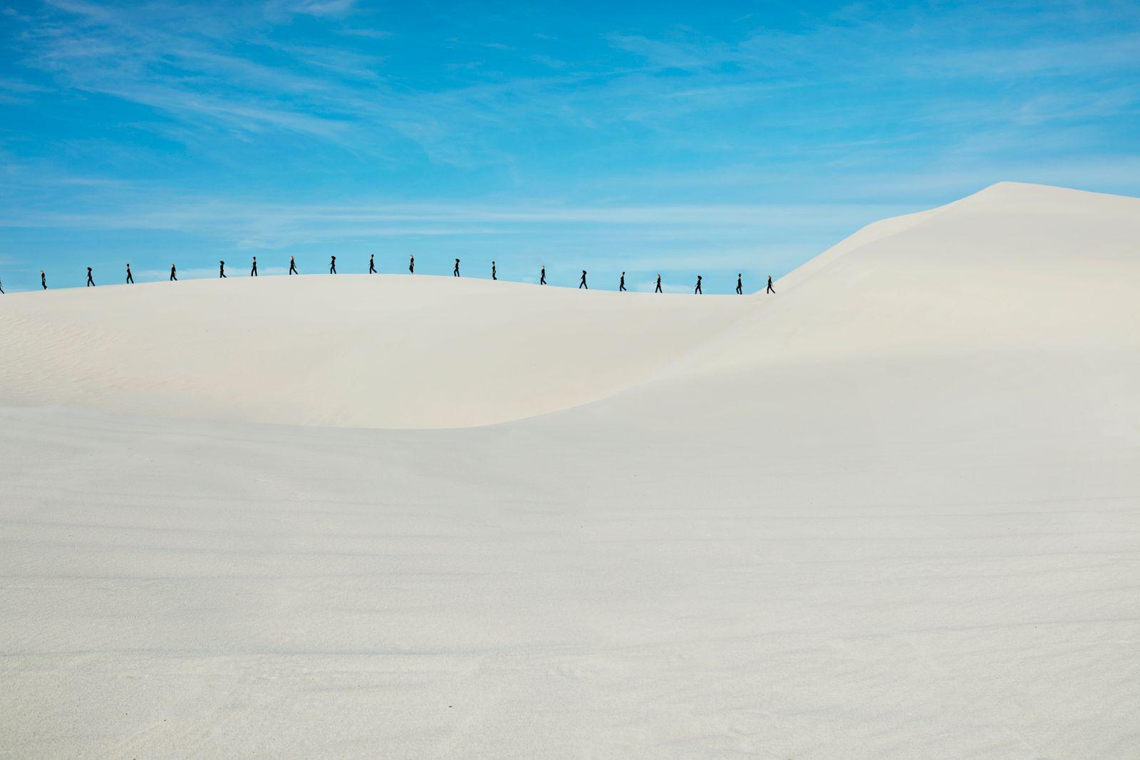 Distant multiple image of fashion models walking on sandy hill at desert