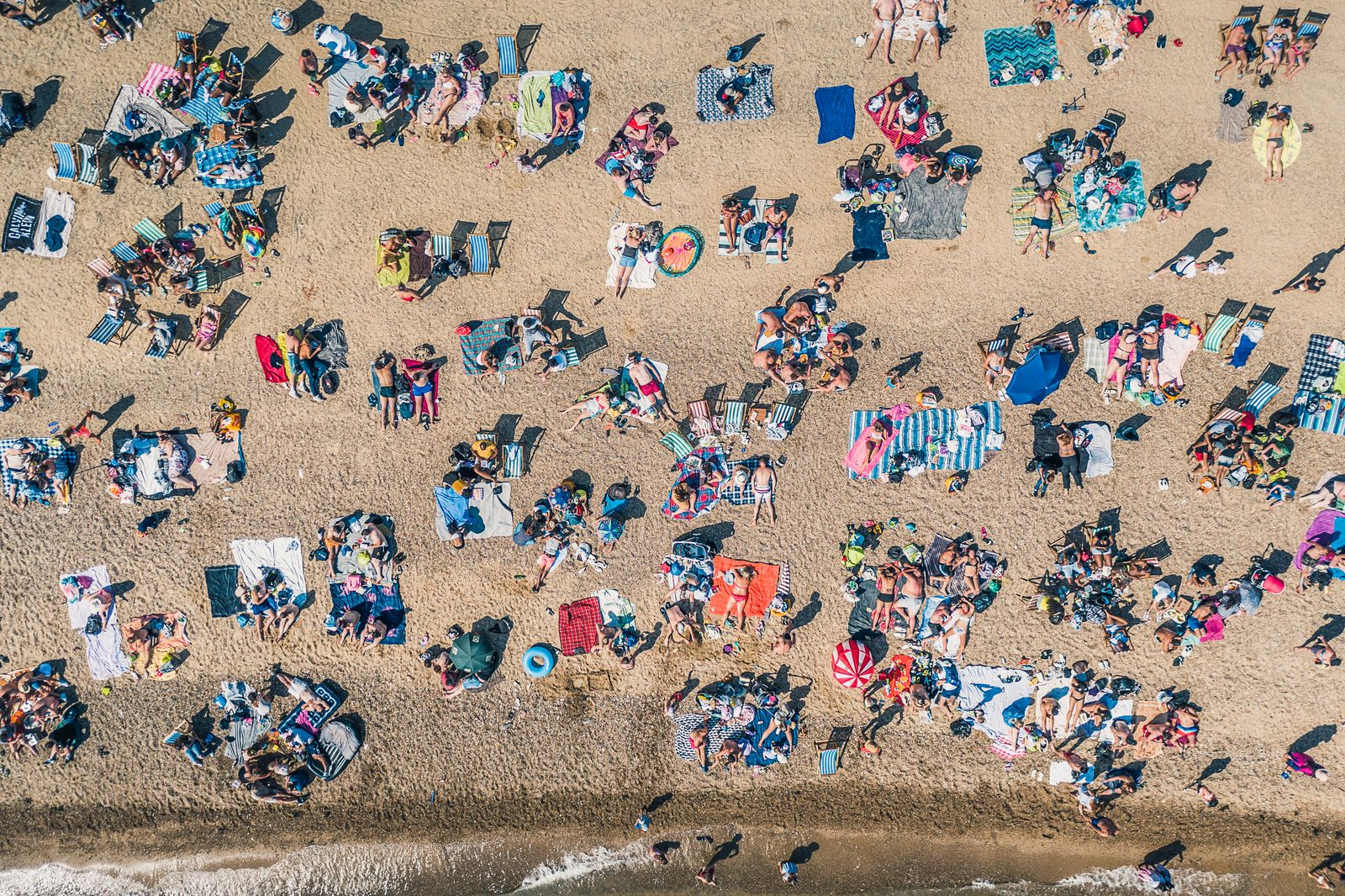 Sunbathers relaxing on Southend Beach as seen from directly above, Southend-on-Sea, Essex, United Kingdom