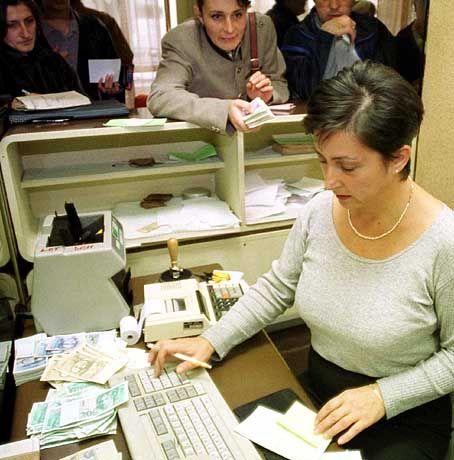Eine Bankangestellte in Montenegros Hauptstadt Podgorica zahlt Gehälter und Renten in Mark aus