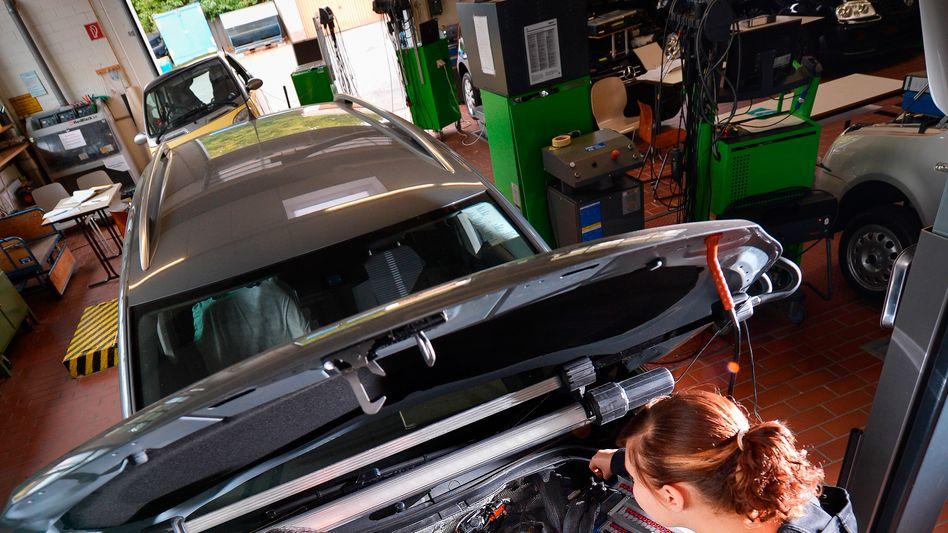 Kfz-Mechaniker bei der Arbeit: Volkswagen bekommt mit dem Rückruf mehrerer Millionen Autos wohl ein massives Kapazitätsproblem