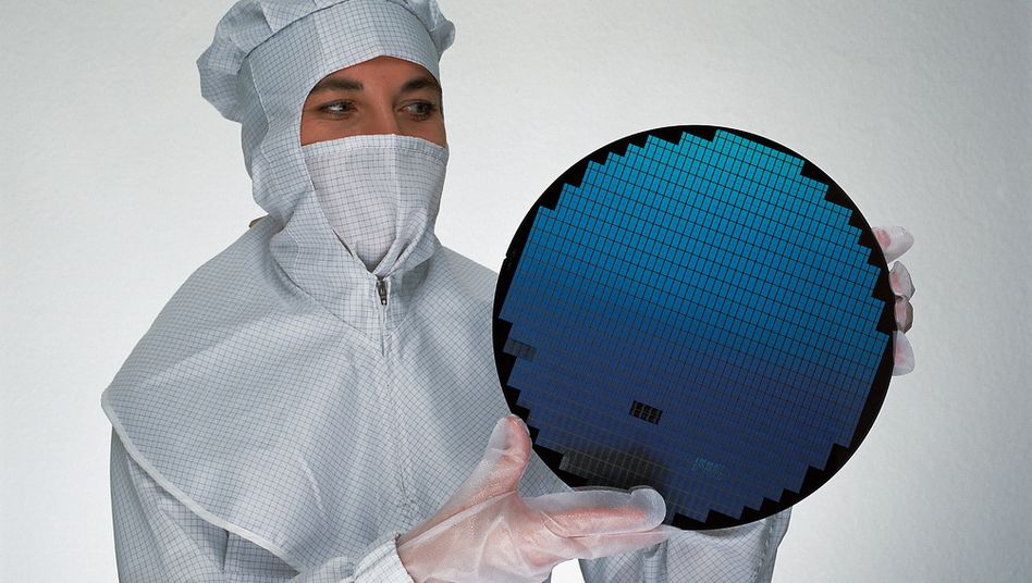 Chiphersteller: Eine Infineon-Mitarbeiterin mit einem Wafer, der Grundplatte für die Fertigung mikroelektronischer Bauelelemente