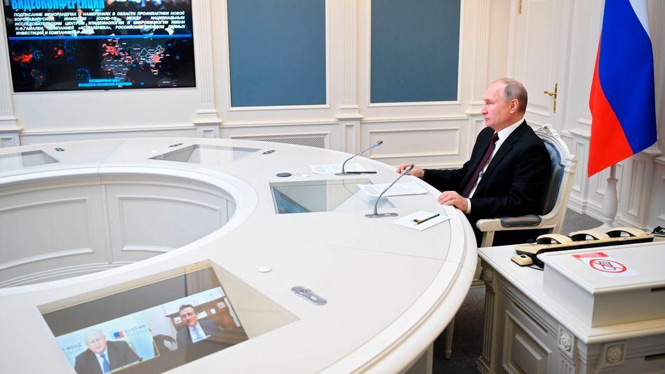 Prestigeerfolg: Russlands Präsident Wladimir Putin in der Videokonferenz mit Gamaleya-Institutschef Alexander Ginzburg und Astrazeneca-Chef Pascal Soriot
