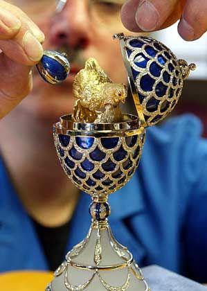 Neues Osterhennen-Ei: Ein Mitarbeiter der Firma Victor Mayer in Pforzheim setzt ein Miniaturei in eine Henne aus 18-karätigem Gold ein. In der Miniatur sind vier Hasen aus Gold eingearbeitet. Das äußere Ei ist mit 1582 hochfeinen Brillanten besetzt und besteht aus Gelb- und Weißgold sowie blauem Feueremaille
