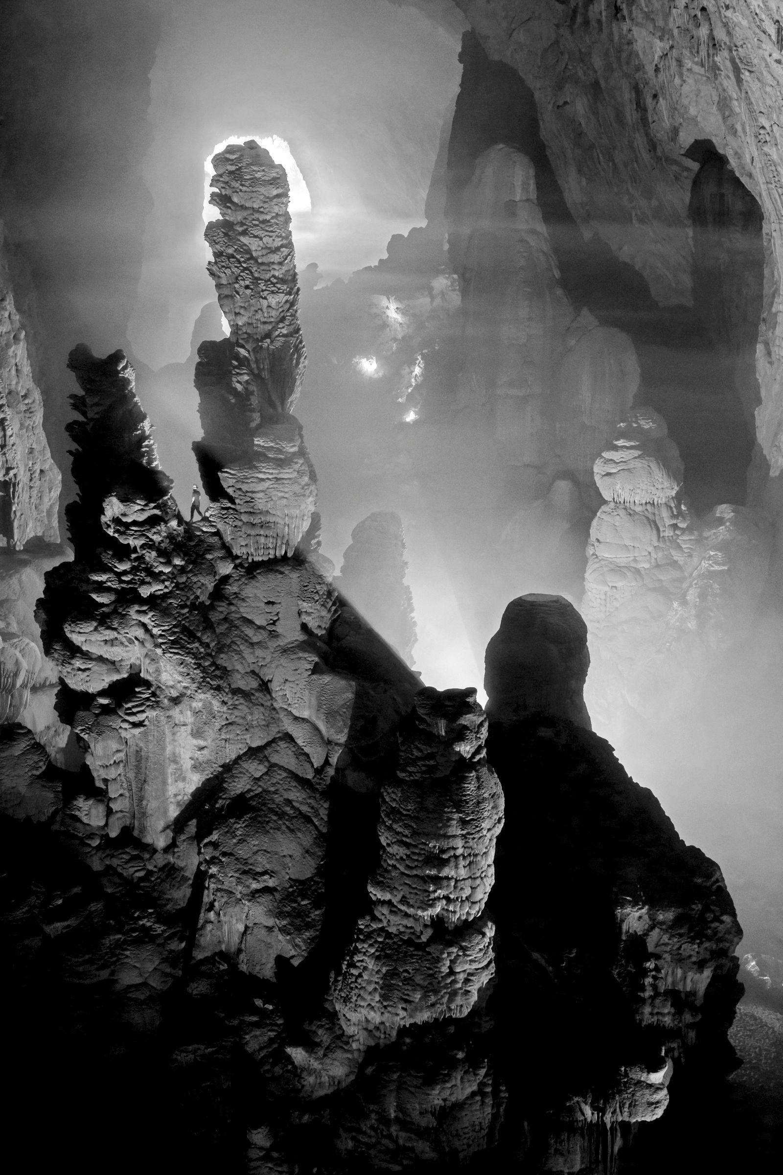 EINMALIGE VERWENDUNG A caver is dwarfed by massive stalagmites in Hang Son Doong