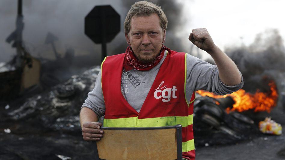 Freut sich: CGT-Mitglied am Dienstag vor einer brennenden Barrikade.