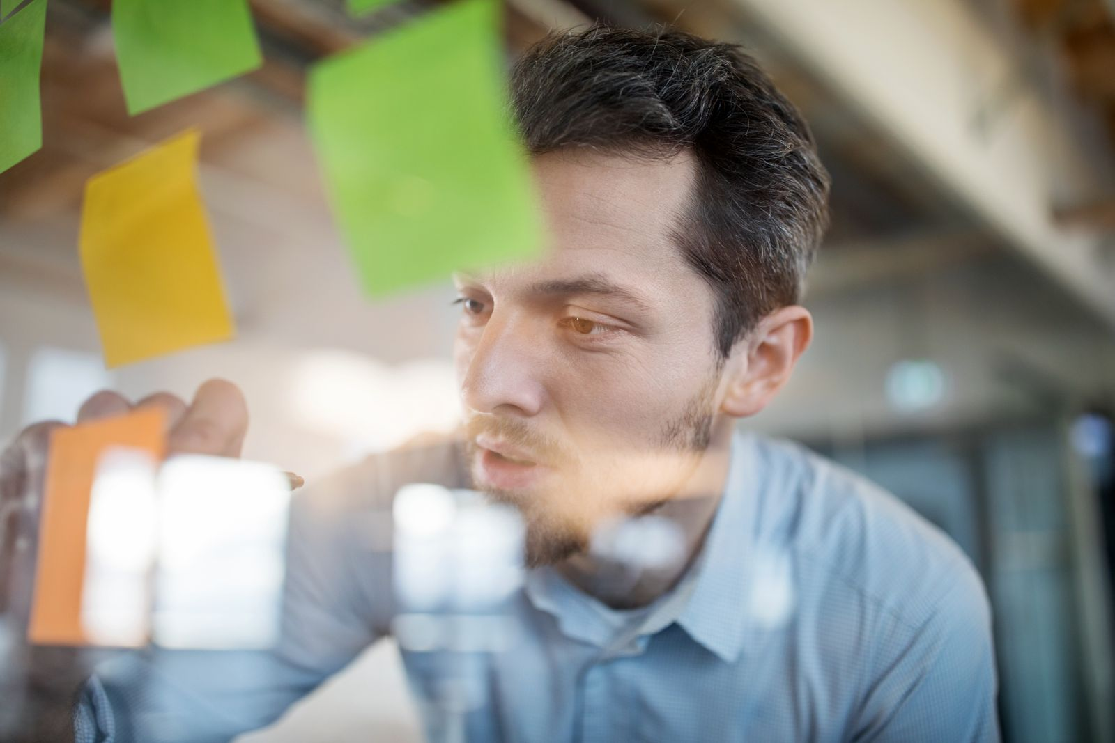 Young businessman writing on adhesive note