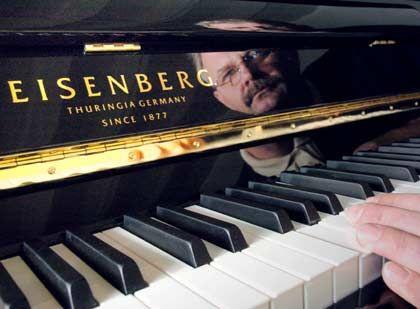 """Wirft einen prüfenden Blick: Fertigungsleiter Gerd Fillipiak mit einem Klavier der Marke """"Eisenberg"""""""