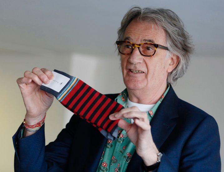 Die Socken? Freihändig? An die Füße? Okay, der Text ist frei erfunden - wir sehen hier Designer Paul Smith mit von ihm kreierten Ringelsocken bei einer Ausstellung seiner Entwürfe in London. Aber die Frage bleibt: Können Sie Ihre Socken im Stehen anziehen, ohne umzufallen?