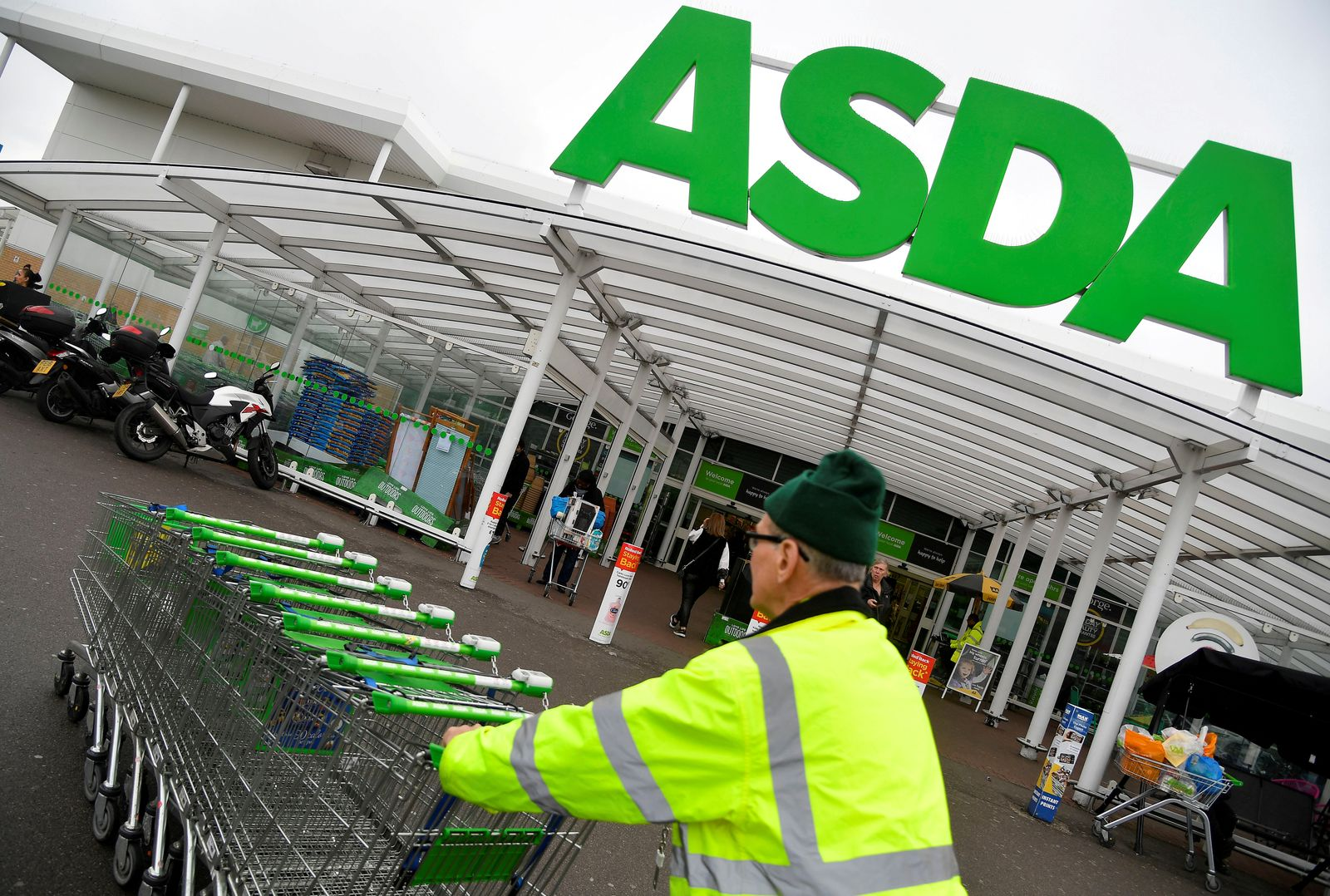 FILE PHOTO: A worker pushes shopping trolleys at an Asda store in London
