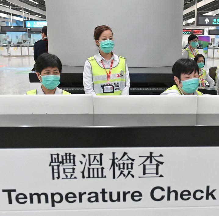 Mitarbeiter des Hongkonger Gesundheitswesens befragen und untersuchen am Bahnhof West Kowloon Station Reisende auf ihren Gesundheitszustand