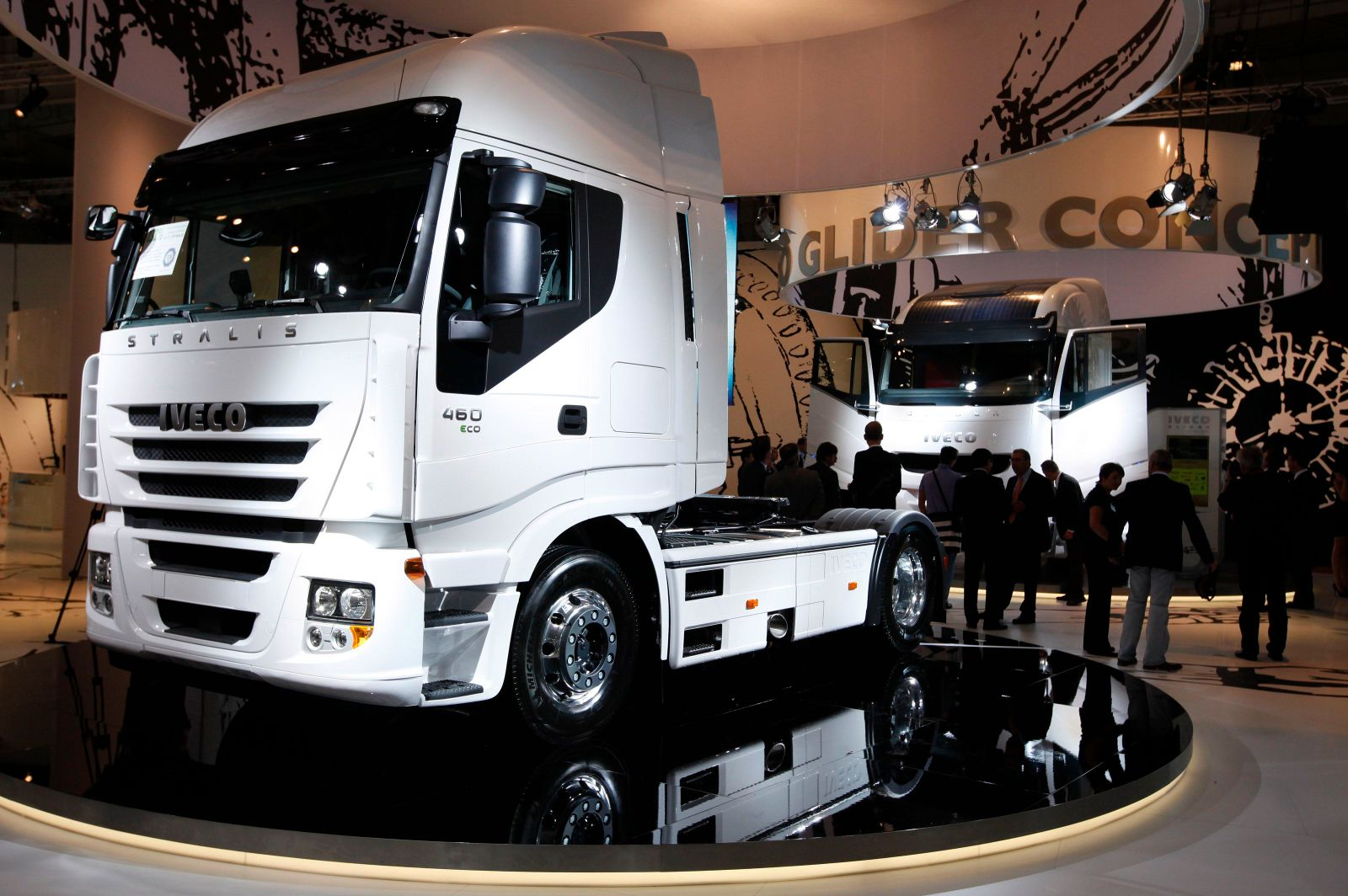 Visitors walk along heavy trucks at Fiat Iveco exhibition area at IAA commercial vehicles trade fair in Hanover