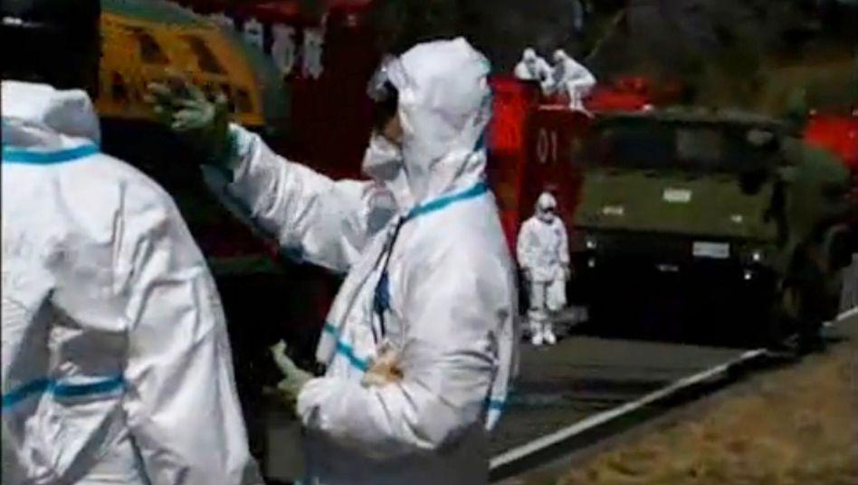 Verzweifelter Kampf: Männer bringen Wasserwerfer gegen das Kraftwerk in Fukushima in Stellung