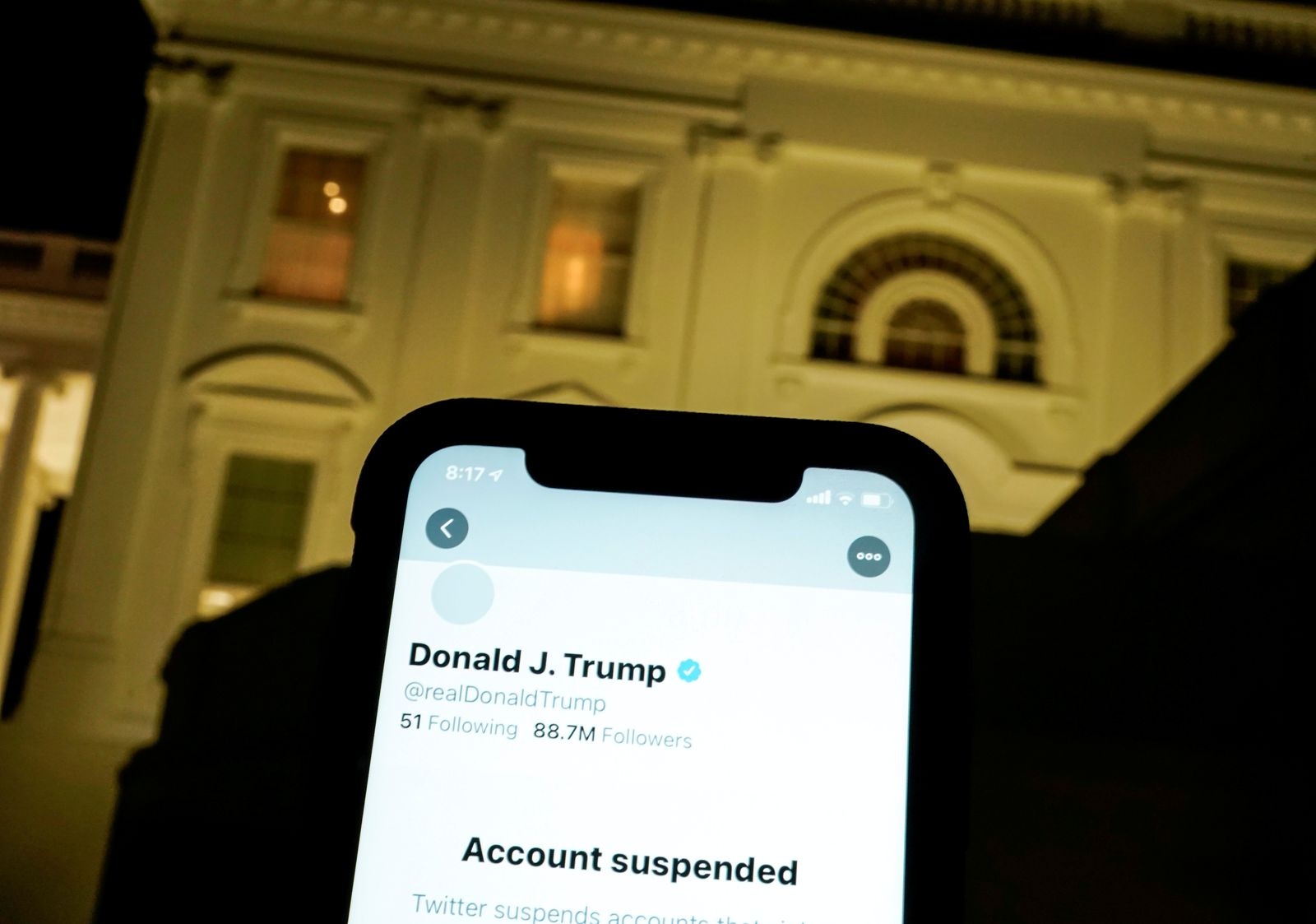 FILE PHOTO: A photo illustration shows the suspended Twitter account of U.S. President Donald Trump on a smartphone and the White House in Washington