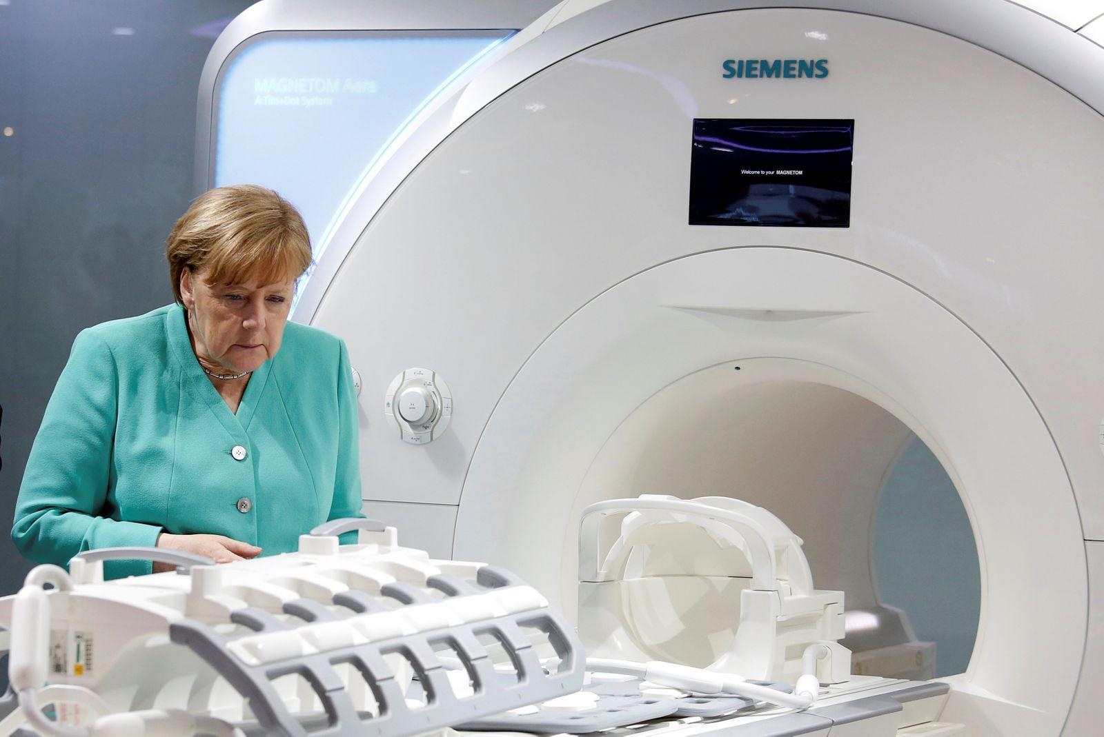 FILE PHOTO: German Chancellor Angela Merkel checks a magnetic resonance imaging machine as she visits Siemens Healthineers in Shenzhen