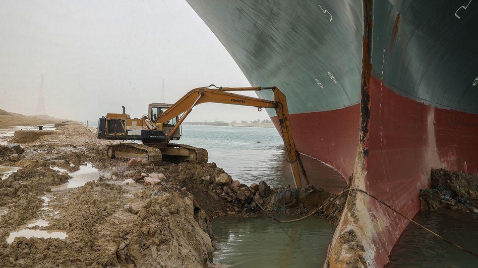 """Große Aufgabe, viel Optimismus: Unermüdlich versucht dieser tapfere, noch unbekannte Baggerführer, die """"Ever Given"""" im Suezkanal freizuschaufeln"""