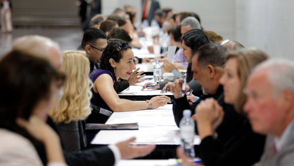 Job seekers have their resumes reviewed at a job fair expo in Anaheim, Calif. A Chapman University forecast says the country and state's economic recovery will continue slowly.
