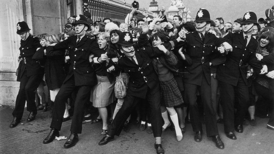 Treue Fans:Die Polizei hat 1965 ganz schön zu tun, Fans davon abzuhalten, den Buckingham Palace zu stürmen. Anlass: Die Beatles bekommen von der Königin einen Orden verliehen.