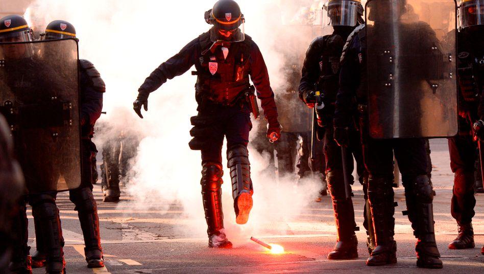 Ein französischer Polizist tritt einen Bengalo weg