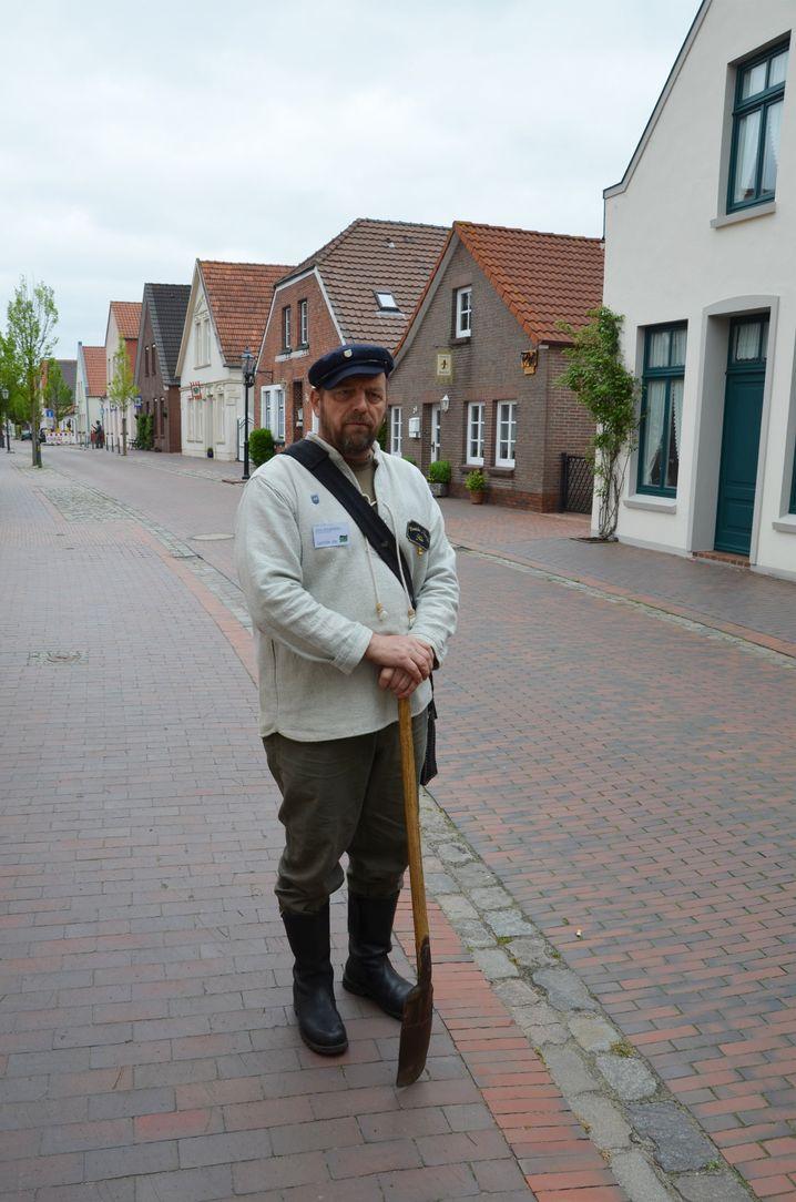 Dirk Arnskötter hält einen Spaten zwischen den Händen - er macht in Neustadgödens Stadtführungen als Koyer, wie die Deichbauarbeiter hießen.