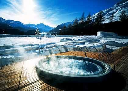 """Genuss im Schnee: Statt durch Glas blicken Gäste des """"Suvretta House"""" im Außen-Whirlpool direkt auf das Hotel umgebende Berge"""