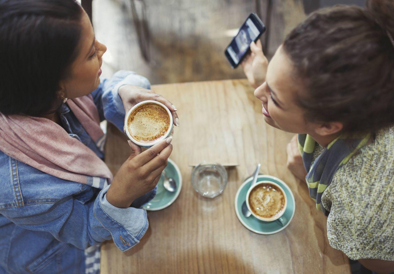 EINMALIGE VERWENDUNG Junge Frauen trinken Kaffee