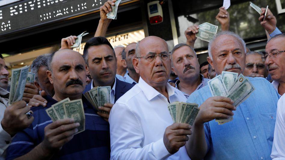 Werden Sie Erdoğans Aufruf erneut folgen? Vor einer Wechselstube drängen sich Mitte August 2018 Geschäftsleute mit US-Dollar in der Hand. Sie wollen nach einem Aufruf des türkischen Präsidenten demonstrativ Dollar- und Euro-Ersparnisse verkaufen, um die türkische Lira zu stützen.