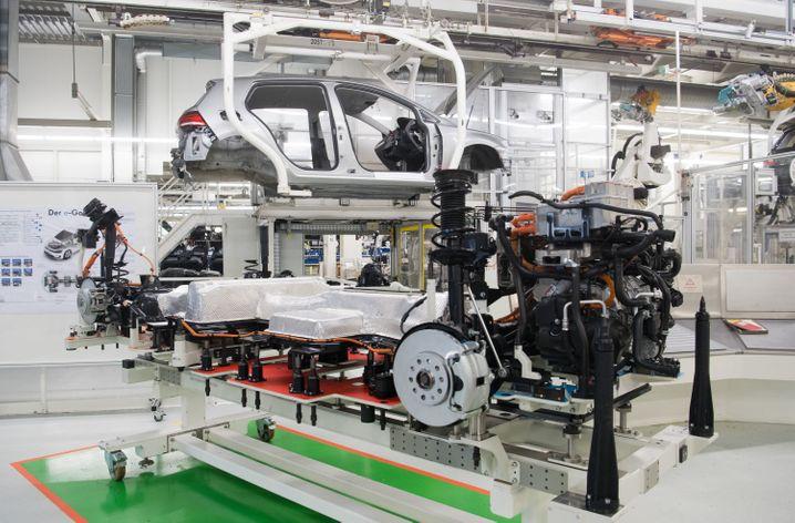 Konkurrenz in Sicht: Modell des e-Golf vor Produktionslinie des VW Golf in Wolfsburg