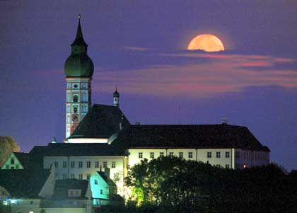 Goldgelb steht am Donnerstagmorgen (26.08.1999) der zunehmende Mond ber dem Kloster Andechs (Landkreis Starnberg), das auf dem Heiligen Berg oberhalb des bayerischen Ammersees steht. In der Nacht zum Freitag (27.08.1999) wird der Erdtrabant dann in seiner vollen Grˆþe als Vollmond erscheinen. dpa/lby