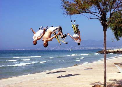 Dreifacher Salto: Junge Hüpfer zeigen an einer Strandpromenade auf Mallorca, was mit Stelzen alles möglich ist