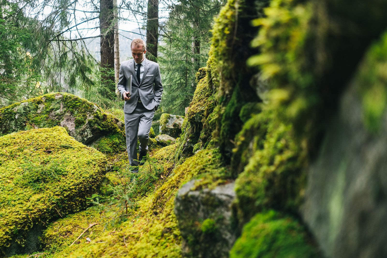 Business man walks through forest with laptop in the morning