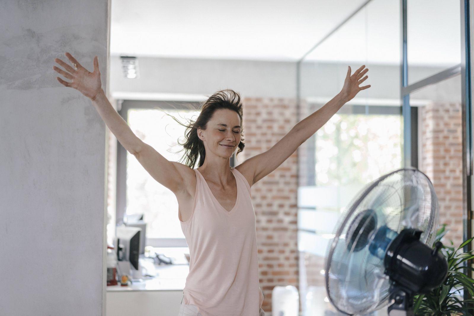 Businesswoman in office enjoying breeze from a fan model released Symbolfoto property released PUBL