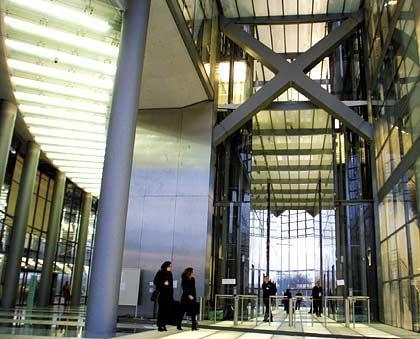 Glas überall: Auch beim Heraustreten aus den Aufzugsgruppen genießt der Besucher den Blick ins Weite. Die Grundfläche des Post-Turms hat die Form zweier zueinander versetzter Halbellipsen. Das Hochhaus wurde in den Jahren 2000 bis 2002 gebaut und liegt idyllisch in den Bonner Rheinauen an der Charles-de-Gaulle-Straße.