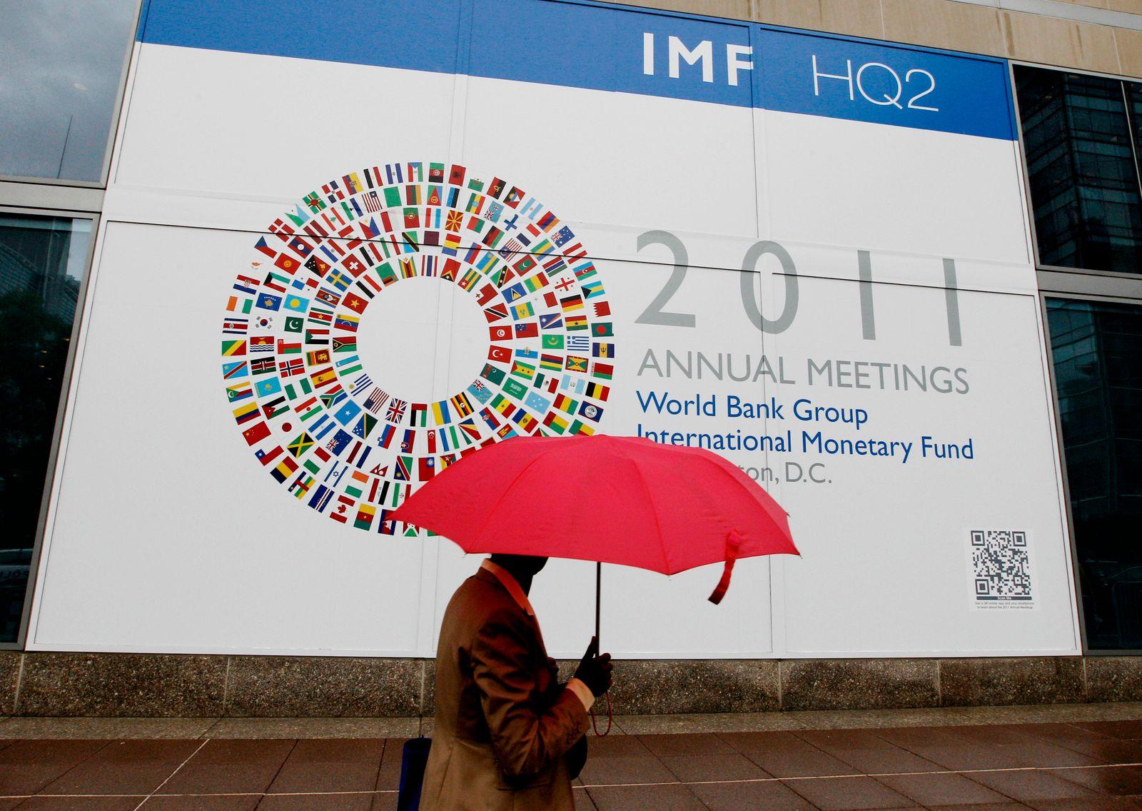 NICHT VERWENDEN Passant mit Regenschirm beim IWF-Treffen