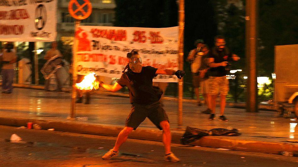 Vor dem Athener Parlament: Ein Maskierter wirft einen Brandsatz. Später am Mittwochabend beruhigte sich die Lage.