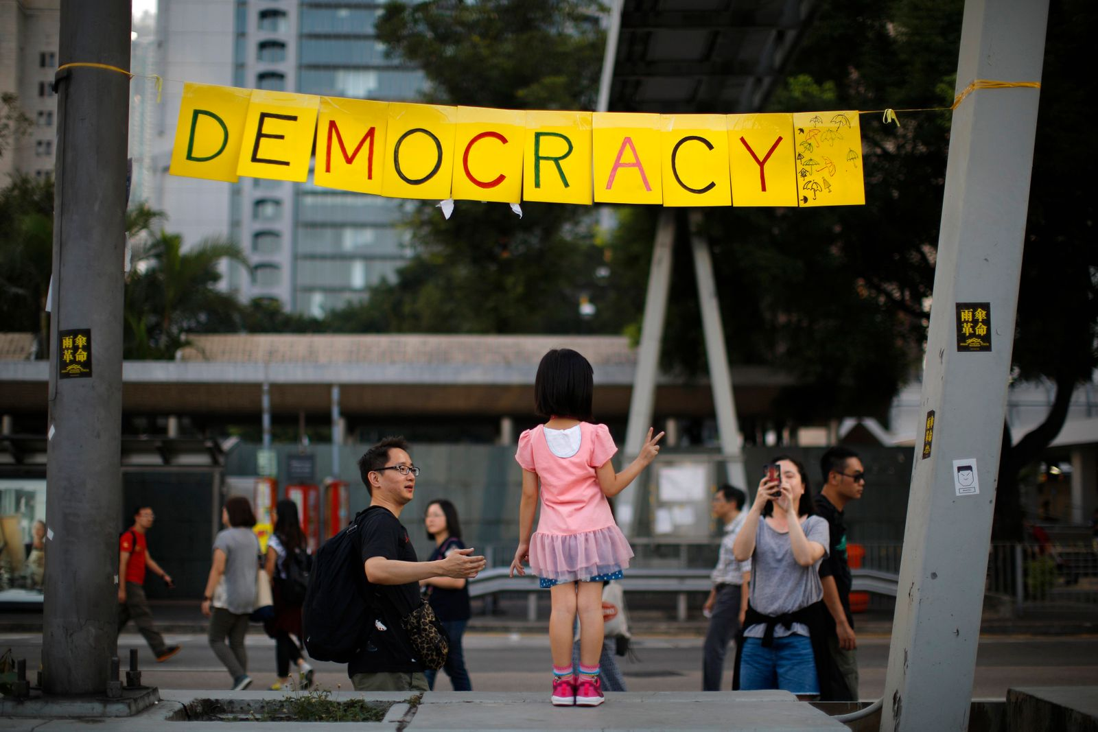 A girl poses next to a sign at an area blocked by pro-democracy protesters outside of the government headquarters building in Hong Kong
