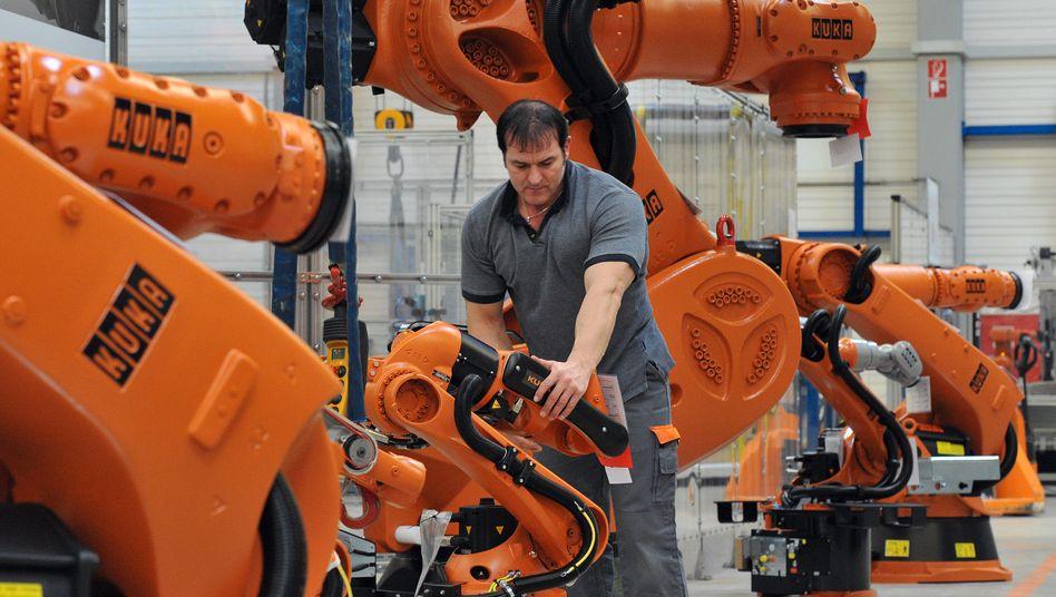 Arbeit an einem Roboter bei Kuka: Deutsche Mittelständer bunkern Geld