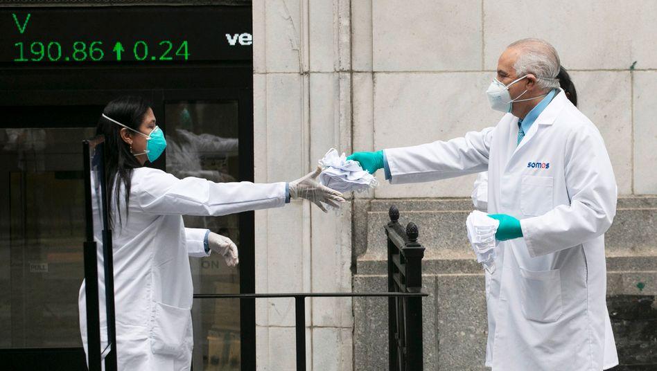 Mitarbeiter aus dem Gesundheitswesen verteilen Mundschutze an der New Yorker Börse