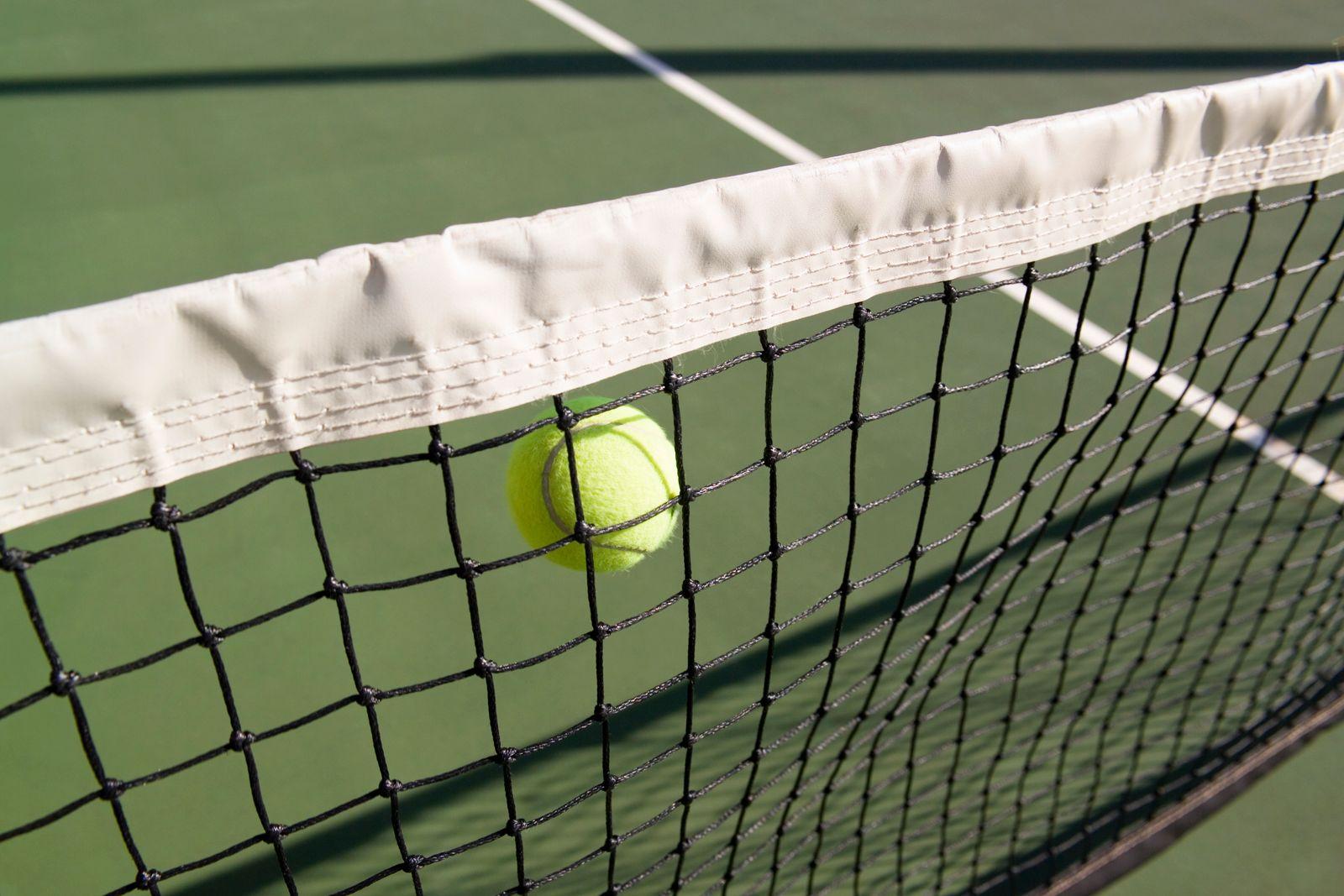 A tennis ball in mid-air next to a tennis net