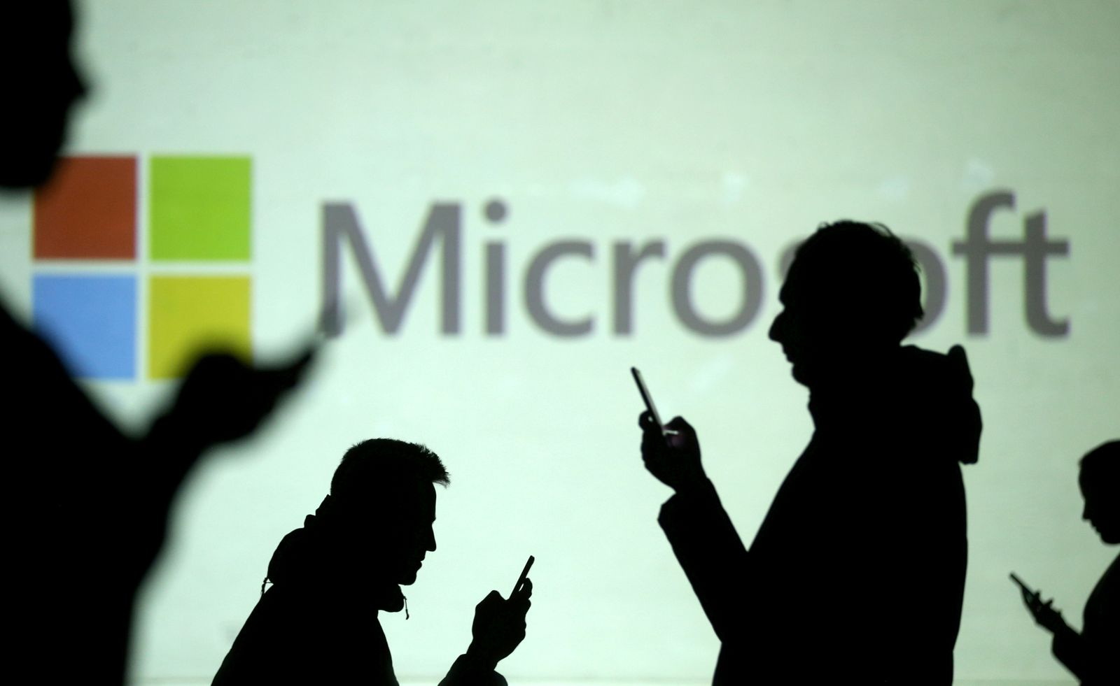 FILE PHOTO: FILE PHOTO: FILE PHOTO: Silhouettes of mobile users are seen next to a screen projection of Microsoft logo in this picture illustration