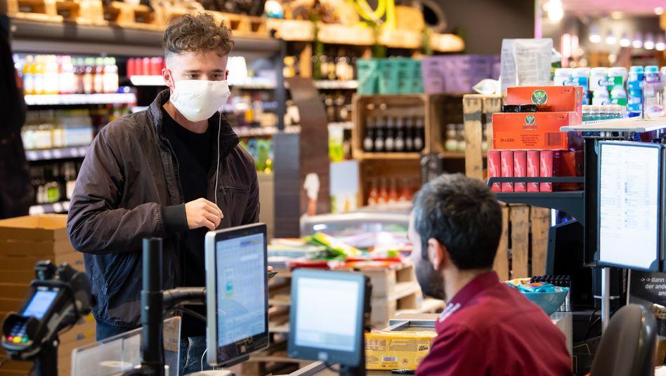 Kunde an Supermarktkasse: Steigende Preise bereiten Ökonomen und Konsumenten gleichermaßen Sorgen