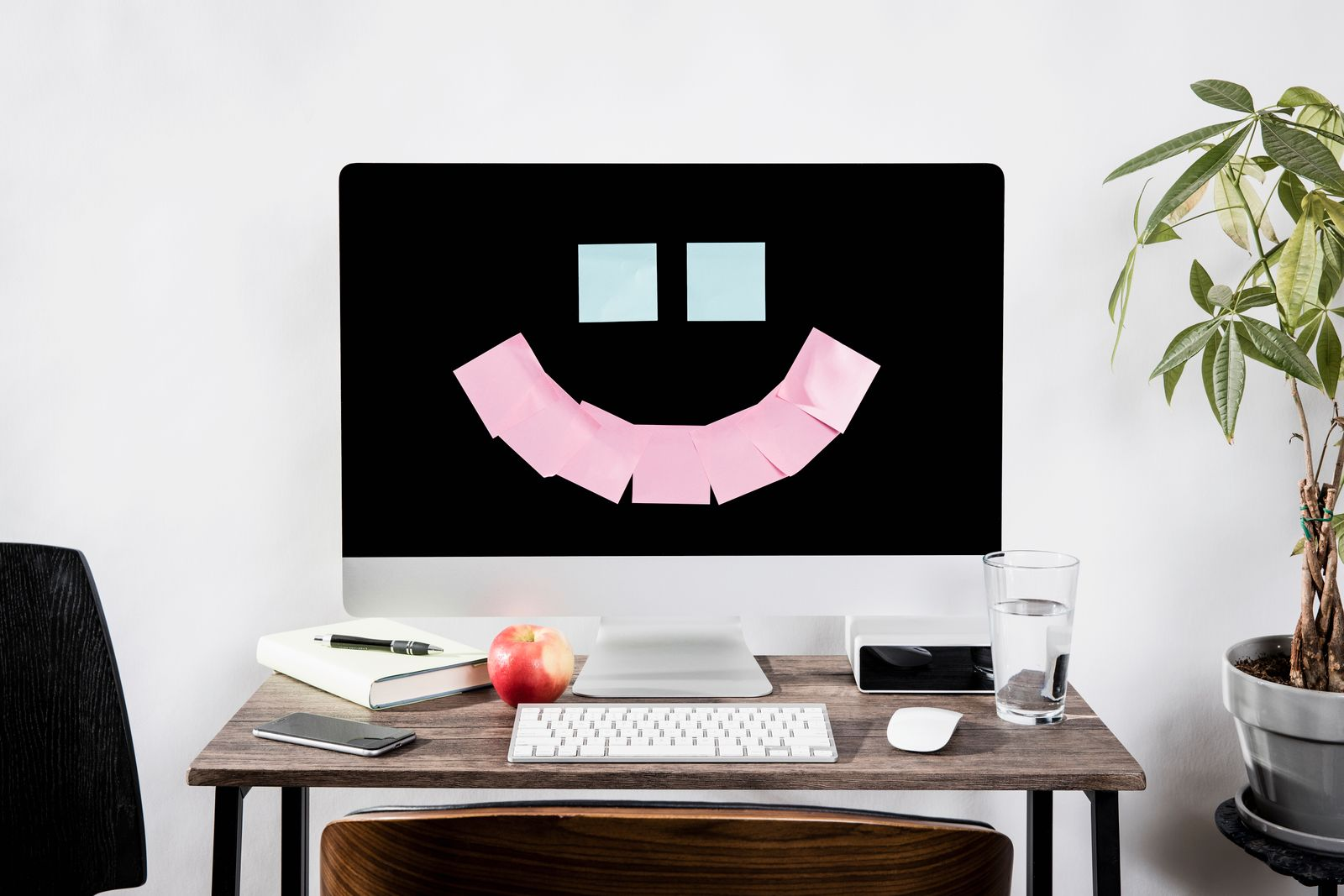 Adhesive notes forming smiley face on computer