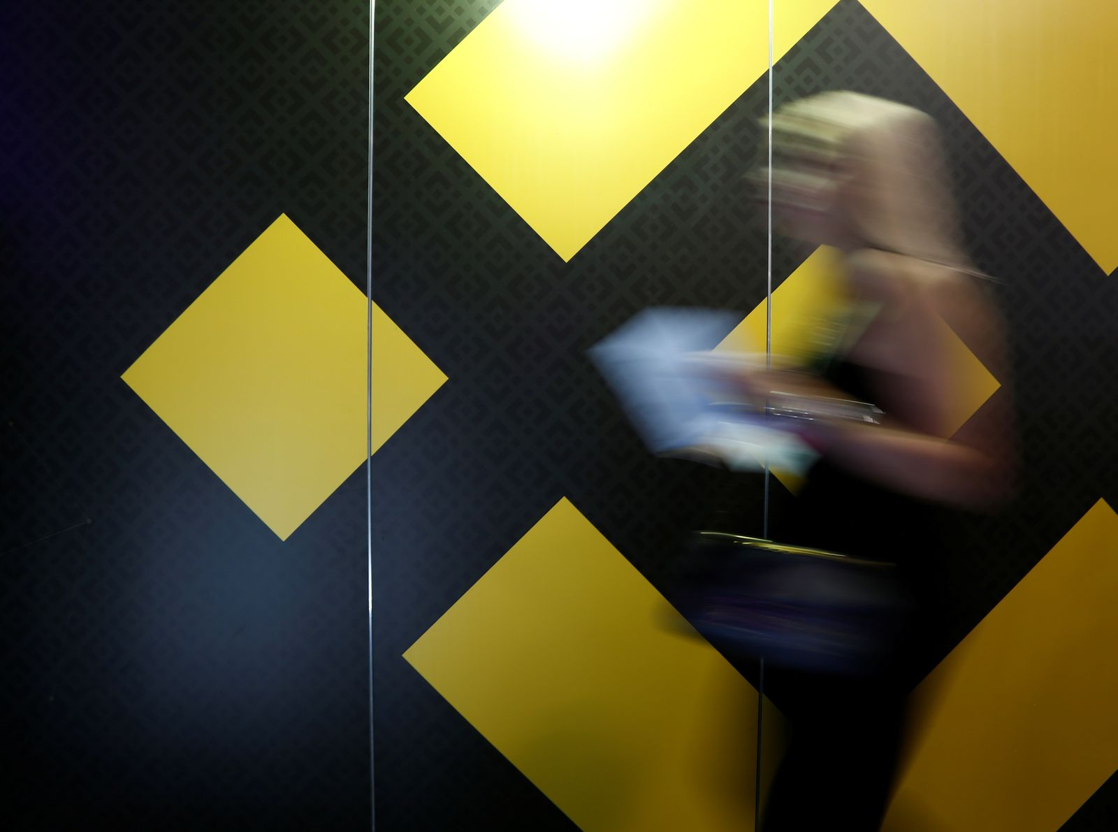 A woman walks past an exhibition stand showing the logo of Binance at the Delta Summit, Malta's official Blockchain and Digital Innovation event promoting cryptocurrency, in St Julian's