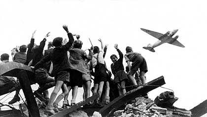 Rosinenbomber: West-Berliner Jungen begrüßen winkend ein US-amerikanisches Transportflugzeug