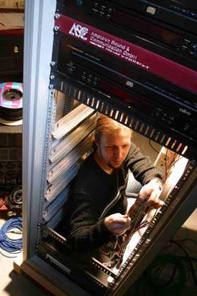 Elektroniktürme: Der Techniker steht im Rack, in das meterhoch weitere Geräte - wie die schwarzen Kästen ganz oben - eingesetzt werden