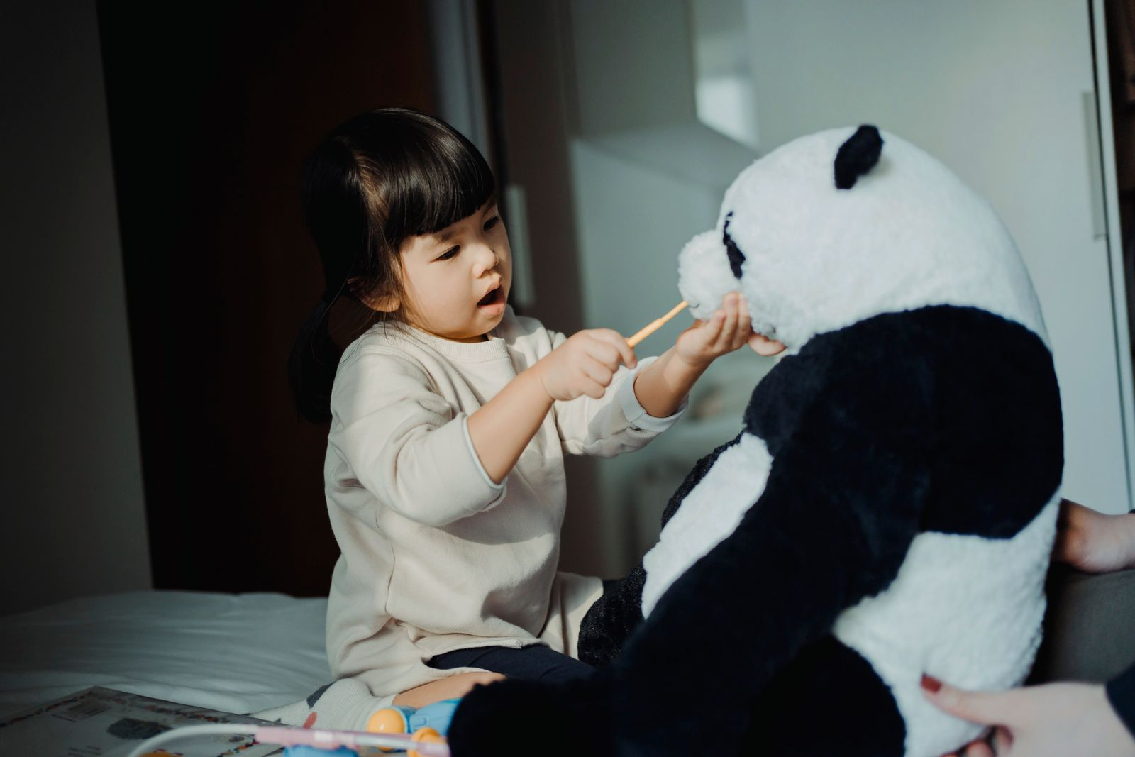 Adorable little Asian girl playing with her soft panda toy, brushing the teeth of the soft panda toy with a toothbrush, playing a dentist game at home