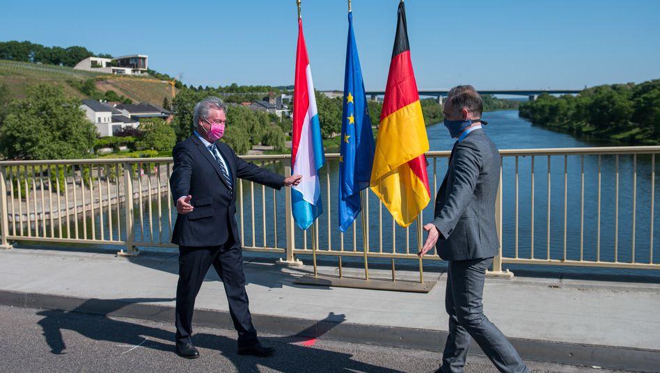 Die Außenminister Jean Asselborn (Luxemburg, l.) und Heiko Maas (Deutschland) begrüßen sich am Samstag auf der Moselbrücke zwischen Schengen und Perl