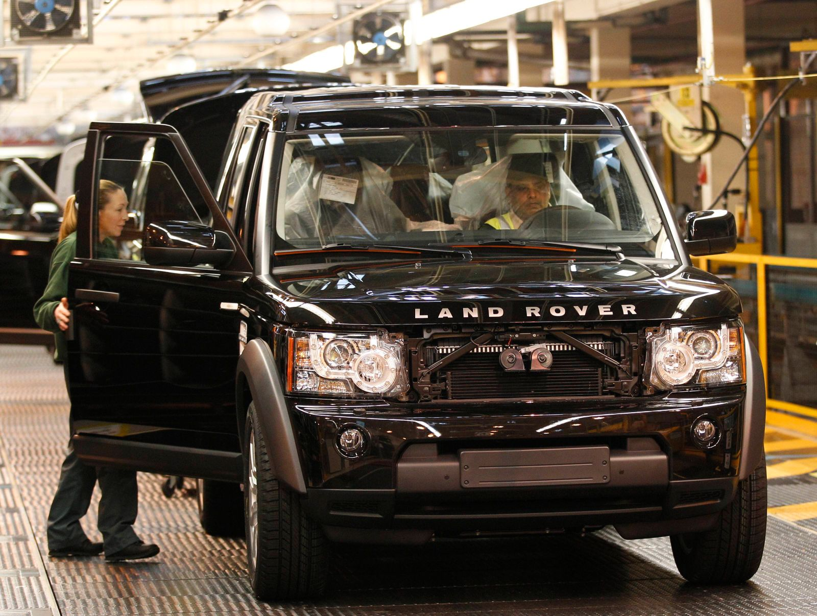 Workers inspect a Land Rover Discovery on the production line at their factory in Solihull
