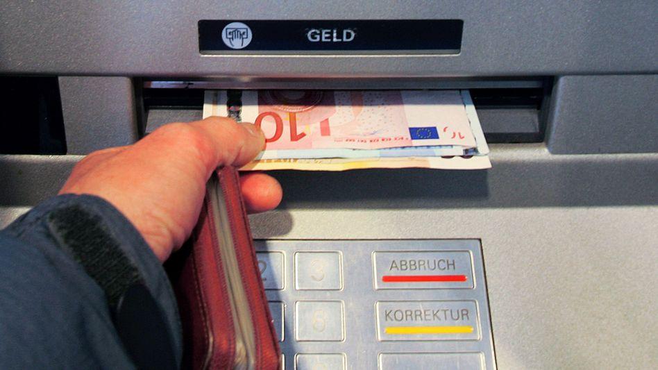 Knietief im Dispo: Noch spuckt der Automat Geld aus - doch das Konto zu überziehen, kann bei vielen Banken teuer werden